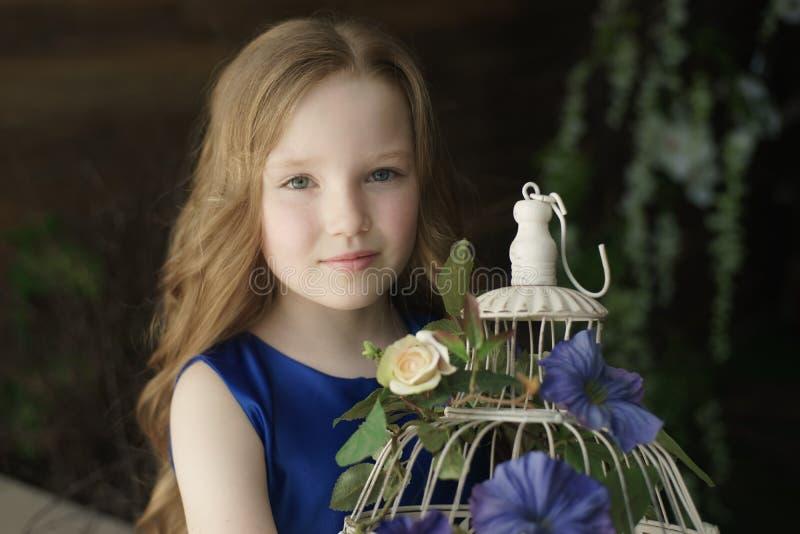 Glückliches kleines Mädchen, das dekorativen Vogelkäfig voll von den Blumen hält Atelieraufnahme im Provence-Artinnenraum lizenzfreies stockbild