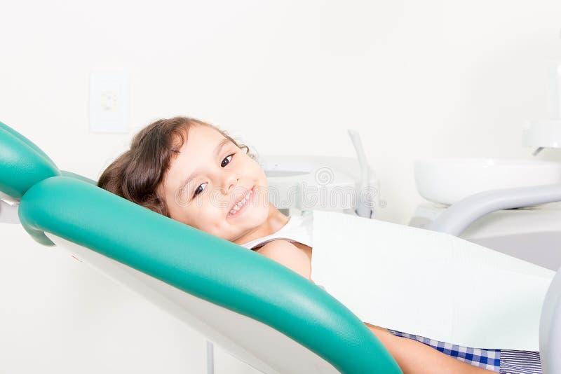 Glückliches kleines Mädchen, das an der zahnmedizinischen Klinik lächelt lizenzfreies stockfoto