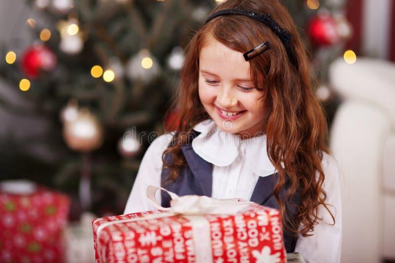 Glückliches kleines Mädchen, das ein Weihnachtsgeschenk hält stockbild