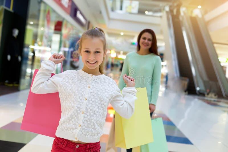 Glückliches kleines Mädchen, das Einkaufstaschen hält und die Kamera betrachtet stockfotografie