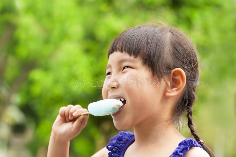Glückliches kleines Mädchen, das Eis am Stiel an der Sommerzeit isst stockfoto