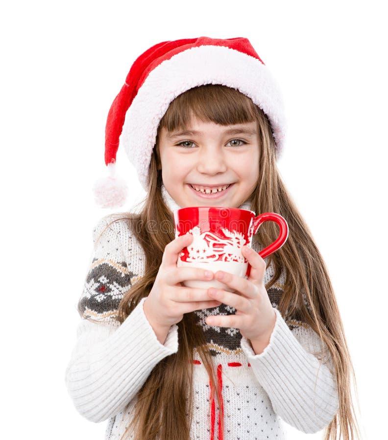 Glückliches kleines Mädchen, das großen Becher des heißen Getränks genießt Lokalisiert auf Weiß stockfotos