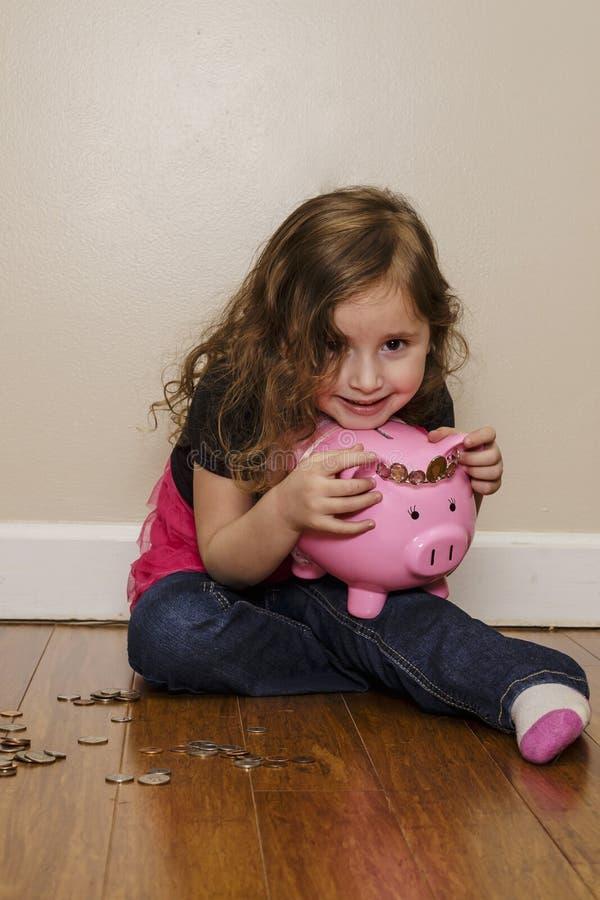 Glückliches kleines Mädchen, das ihr Sparschwein hält lizenzfreie stockbilder