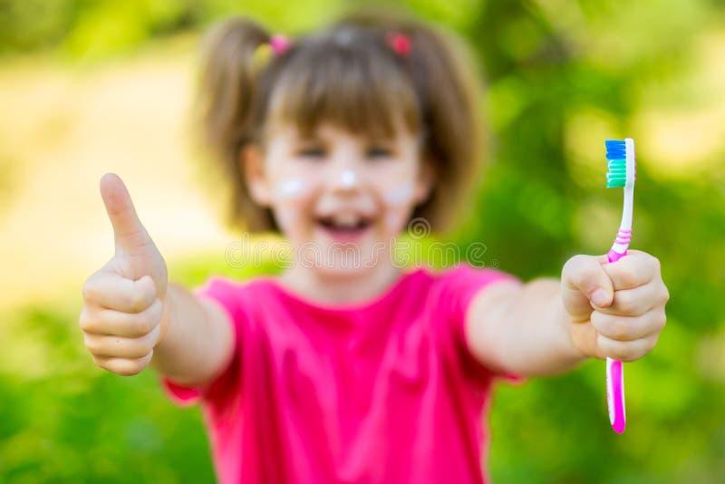 Glückliches kleines Mädchen, das ihre Zähne, Fokus auf Zahnbürste putzt stockfoto