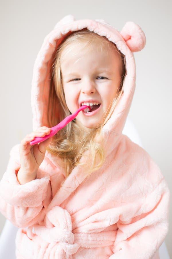 Glückliches kleines Mädchen, das ihre Zähne, rosa Zahnbürste, Mundpflege, Morgen-Nacht gesund putzt stockfotos