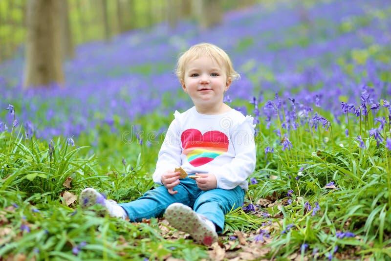 Glückliches kleines Mädchen, das im Glockenblumewald spielt stockfotos
