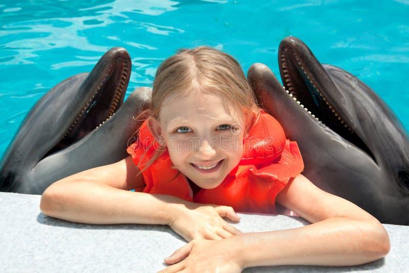 Glückliches kleines Mädchen, das mit zwei Delphinen im Swimmingpool lächelt stockfoto