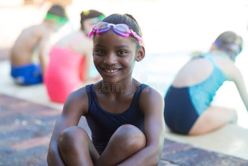 Glückliches kleines Mädchen, das am Poolside sitzt stockfotos
