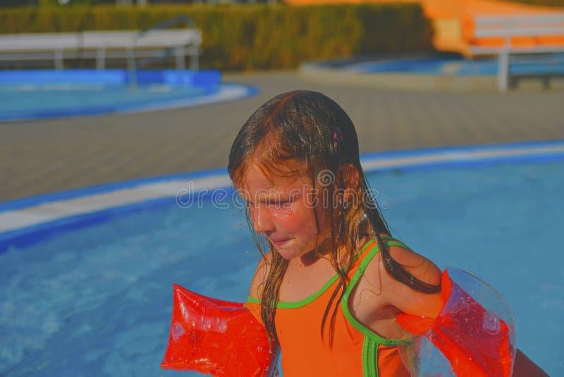 Glückliches kleines Mädchen, das Sommertag im Swimmingpool genießt Nettes Mädchen mit aufblasbaren Armbinden im kleinen Swimmingp lizenzfreies stockfoto