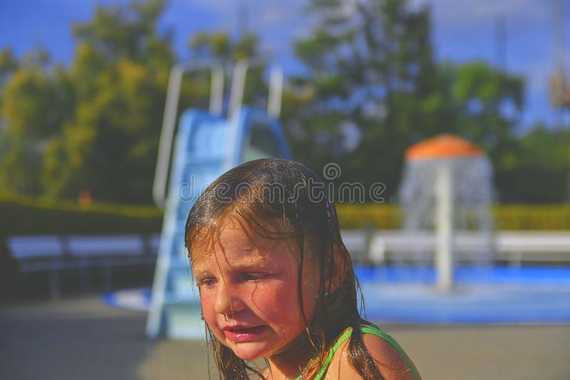 Glückliches kleines Mädchen, das Sommertag im Swimmingpool genießt Nettes Mädchen, das mit Kälte zittert Sommer und glückliches K stockbilder