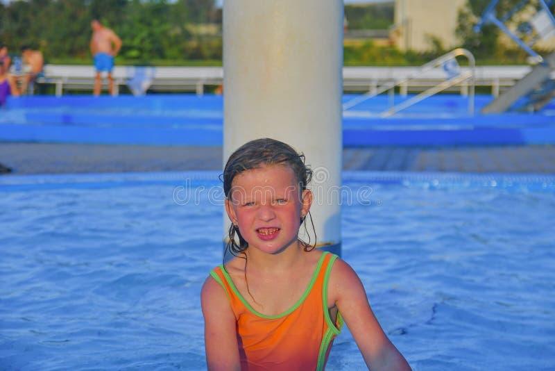 Glückliches kleines Mädchen, das Sommertag im Swimmingpool genießt Nettes Mädchen, das Sommer am Wasserpark genießt Sommer und gl lizenzfreie stockfotos