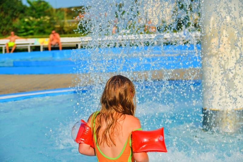 Glückliches kleines Mädchen, das Sommertag im Swimmingpool genießt Mädchen, das zu einer Berieselungsanlage im Spraypool geht Net lizenzfreie stockfotografie