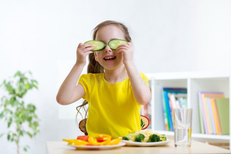Glückliches kleines Mädchen, das Spaß mit Lebensmittelgemüse hat, während Abendessen Gurken vor ihren Augen wie in Gläsern hält lizenzfreie stockfotos