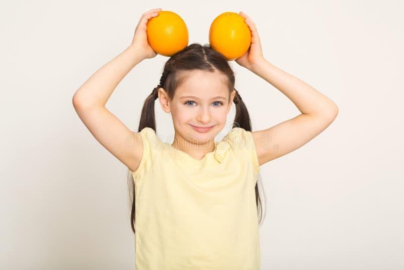 Glückliches kleines Mädchen, das Spaß mit Orangen über weißem Hintergrund hat lizenzfreies stockbild