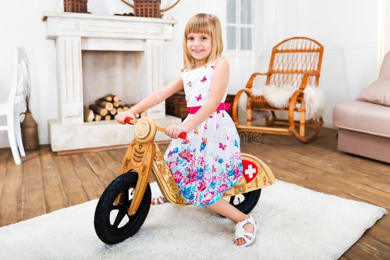 Glückliches kleines Mädchen, das zu Hause ein runbike reitet stockfotografie