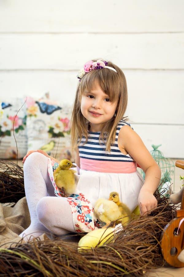 Glückliches kleines Mädchen in einem Kleid mit Blumen auf ihrem Kopf sitzt in einem Nest und hält nette flaumige Ostern-Entlein a stockfotos