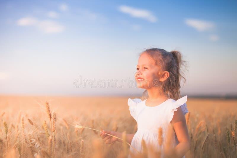 Glückliches kleines Mädchen im Freien am Weizen-Feld Ende des Sommers stockbilder