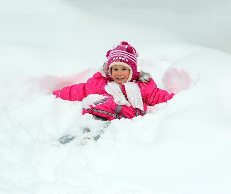 Glückliches kleines Mädchen im Schnee stockfoto