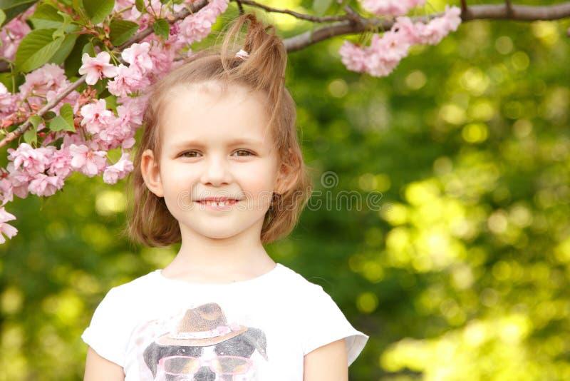 Glückliches kleines Mädchen leckt süße Süßigkeit lizenzfreie stockbilder