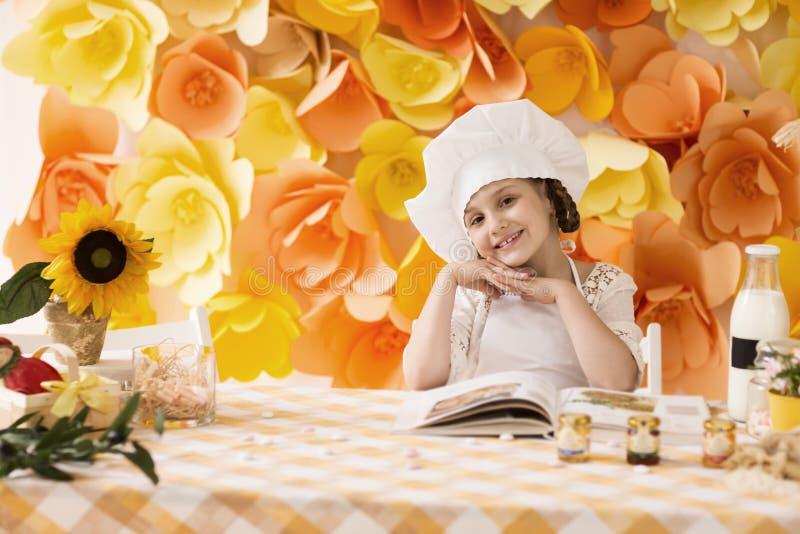 Glückliches kleines Mädchen mit Buchchef bereitet das Frühstück zu und lächelt und wirft für die Kamera auf stockbilder