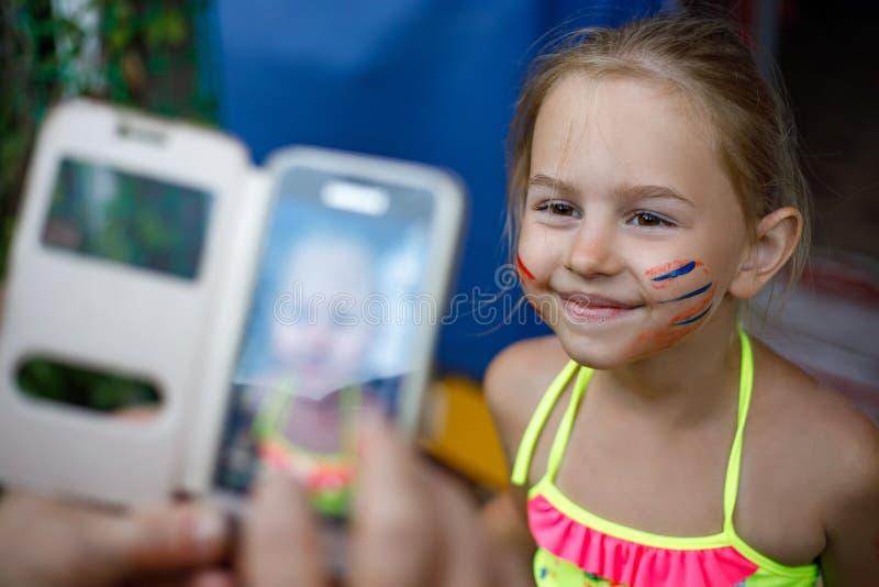 Glückliches kleines Mädchen mit dem gemalten aufwerfenden Gesicht beim auf Smartphone fotografiert werden lizenzfreies stockfoto