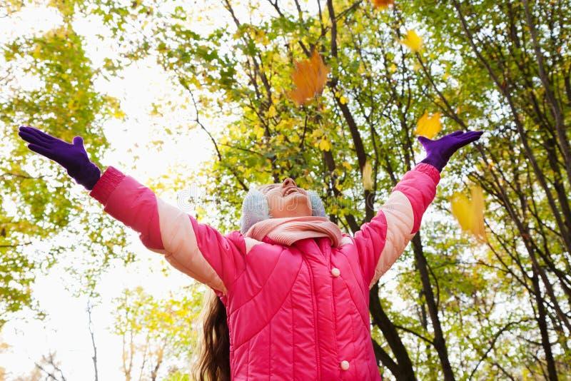 Glückliches kleines Mädchen mit den Händen oben im Herbstpark stockfoto