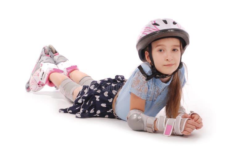 Glückliches kleines Mädchen mit den Rollschuhen und Schutzausrüstung, die auf dem Boden liegen lizenzfreies stockfoto