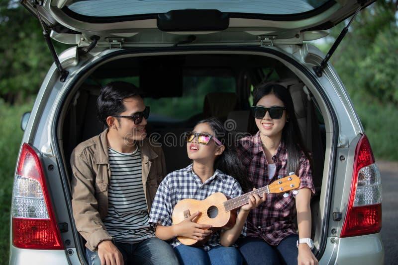 Glückliches kleines Mädchen mit der asiatischen Familie, die im Auto für das Genießen von Autoreise- und Sommerferien im Reisemob lizenzfreie stockbilder