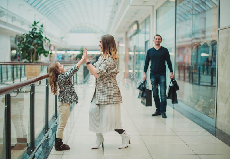 Glückliches kleines Mädchen mit ihrer Mutter im Einkaufswagen und ihren Eltern, die Wochenende in der großen Geschäftsmitte genie lizenzfreie stockfotos