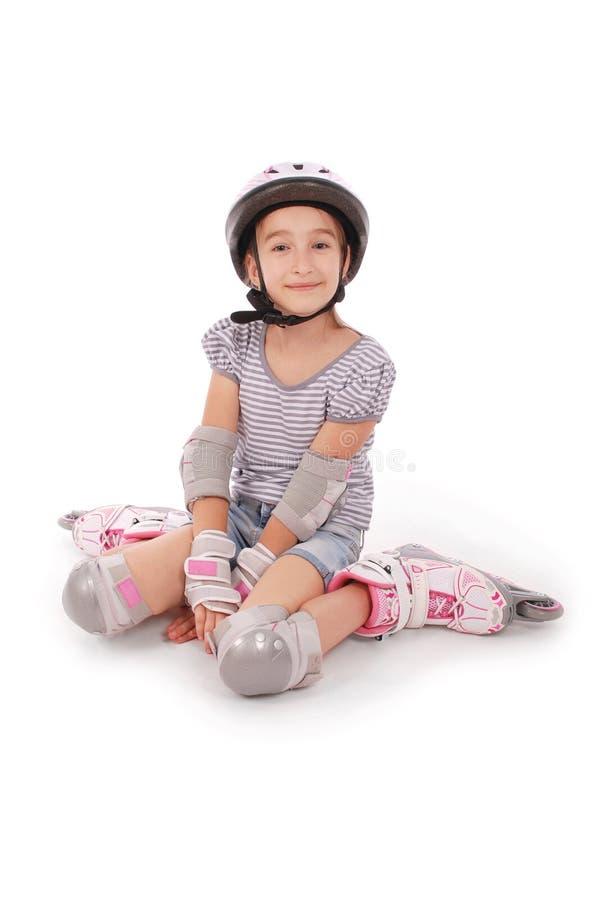 Glückliches kleines Mädchen mit Rollschuhen und dem Schutzausrüstungsstillstehen lizenzfreie stockbilder