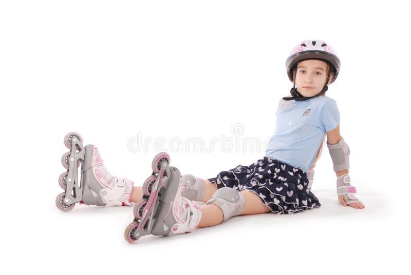 Glückliches kleines Mädchen mit Rollschuhen und dem Schutzausrüstungsstillstehen lizenzfreie stockfotografie