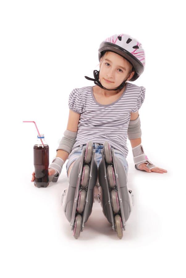 Glückliches kleines Mädchen mit Rollschuhen und dem Schutzausrüstungsstillstehen lizenzfreie stockfotos