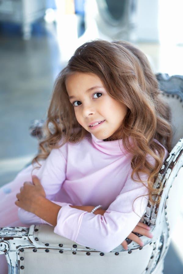 Glückliches kleines Mädchen sitzt im hellen Studio stockfotos