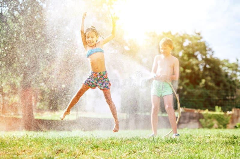Glückliches kleines Mädchen springt unter Wasser, wenn Bruder sie vom Gartenschlauch gießt Heiße Sommertagestätigkeit lizenzfreie stockfotos