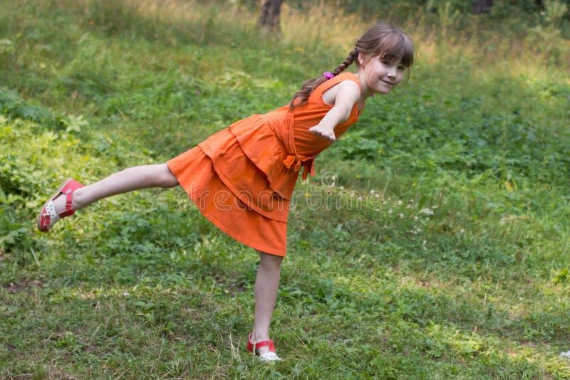 Glückliches kleines Mädchen stellt Vogel auf Gras in sonnigem Wald a dar stockfotos