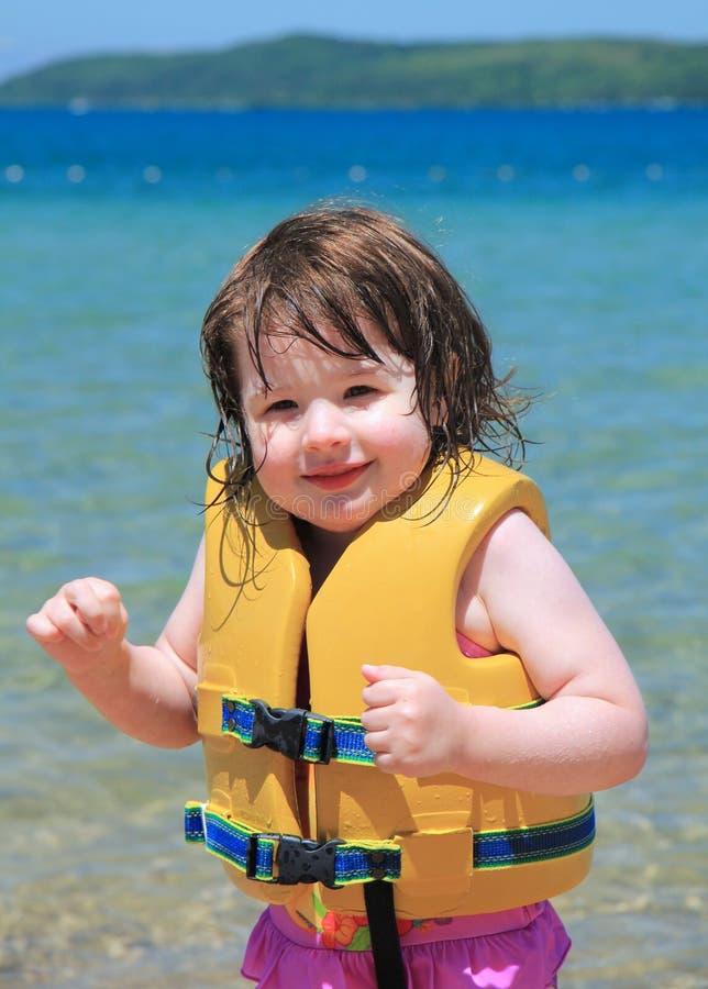 Glückliches kleines Mädchen am Strand stockfotos