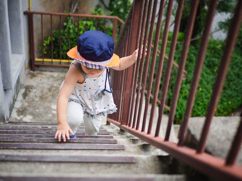 Glückliches kleines nettes Mädchen, welches die Treppe zu upstair klettert glücklich stockfotografie