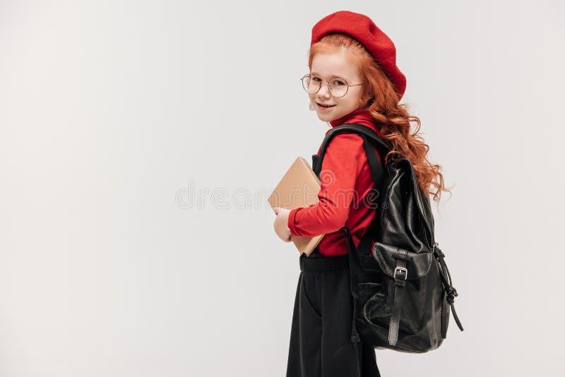 glückliches kleines Schulmädchen mit dem Buch und Rucksack, die Kamera betrachten lizenzfreie stockbilder