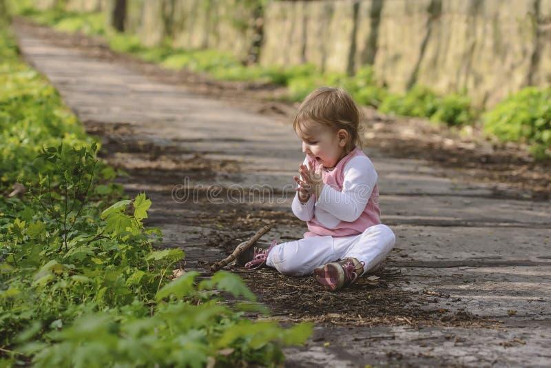 Glückliches kleines spielendes Baby beim Sitzen auf der Straße im Park lizenzfreie stockbilder