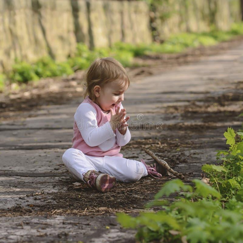 Glückliches kleines spielendes Baby beim Sitzen auf der Straße im Park stockbild