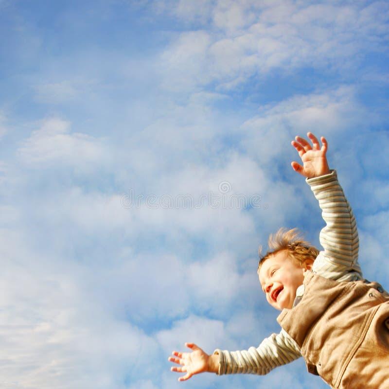 Glückliches Kleinkind auf Himmelhintergrund stockfotografie