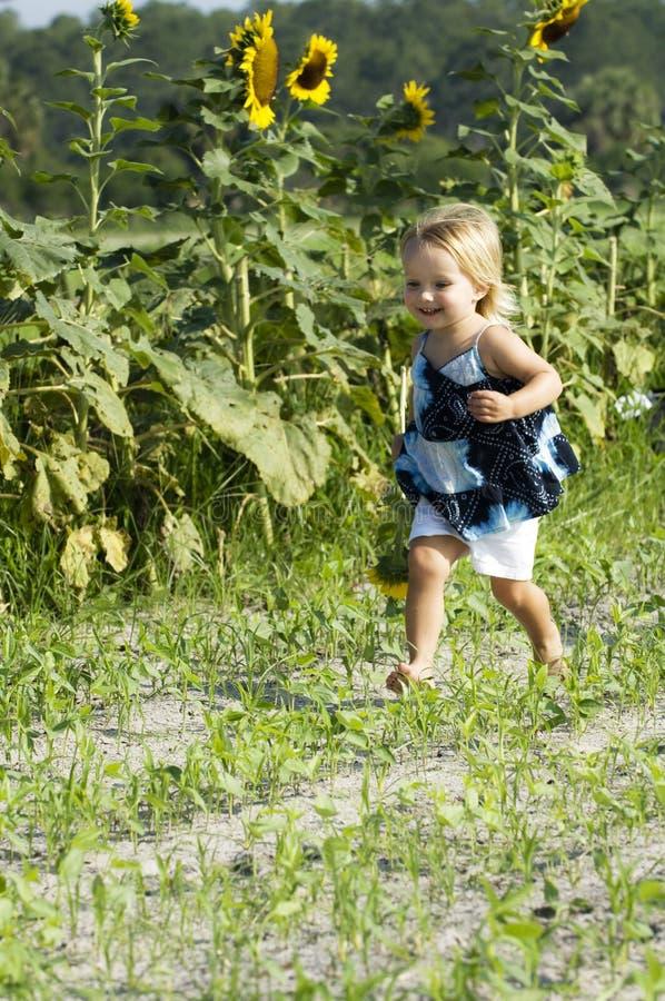 Glückliches Kleinkind, das in Feld läuft stockfoto