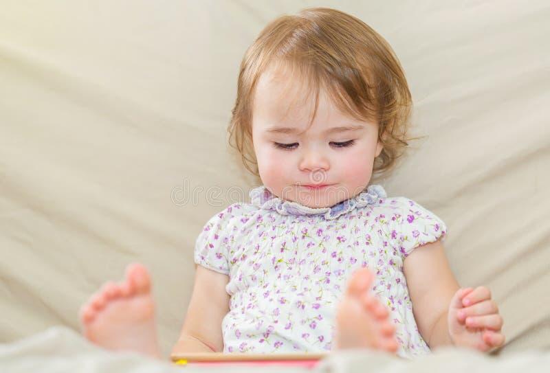 Glückliches Kleinkindmädchen, das einen Tablet-Computer verwendet lizenzfreies stockfoto