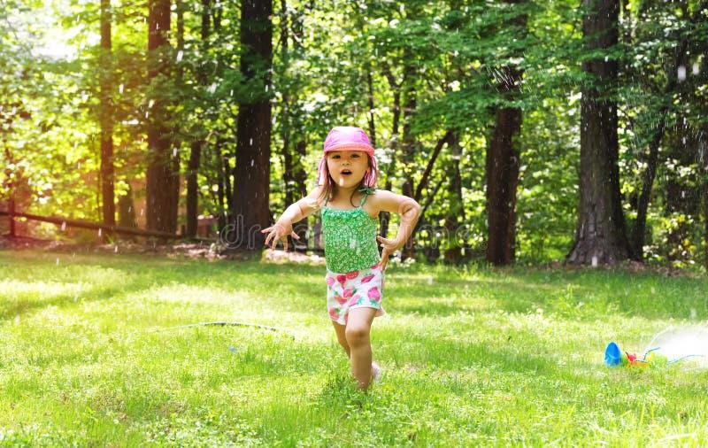 Glückliches Kleinkindmädchen, das in einer Berieselungsanlage spielt lizenzfreie stockfotos
