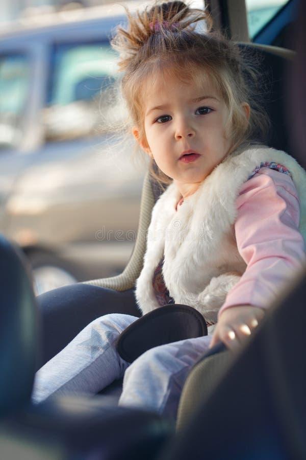 Glückliches Kleinkindmädchen, das im Autositz sitzt stockfoto