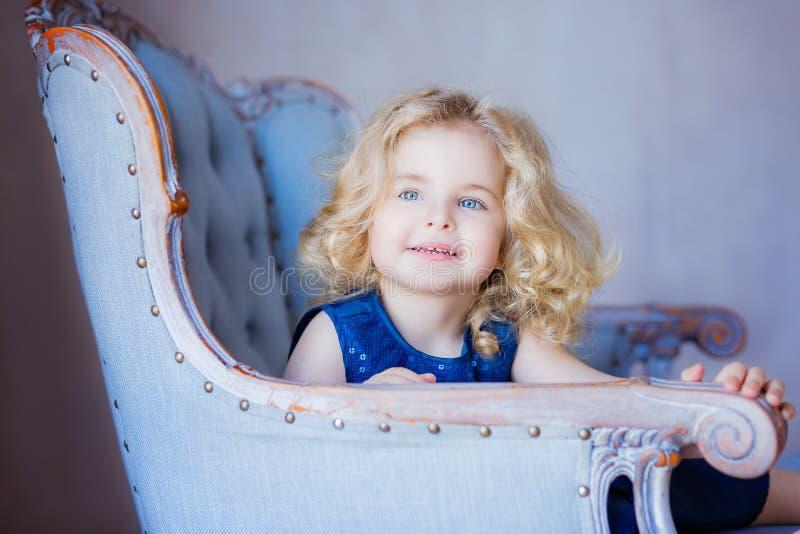 Glückliches Kleinkindmädchen, das im Lehnsessel sitzt Lächeln stockfotografie