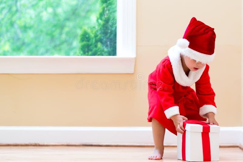 Glückliches Kleinkindmädchen in einem Sankt-Kostüm mit Geschenken stockbilder