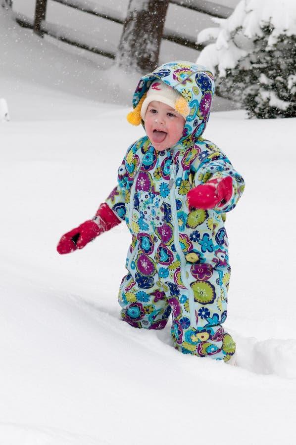 Glückliches Kleinkindmädchen im warmen Mantel und in der Strickmütze draußen werfend herauf Schnee und einen Spaß im Winter haben lizenzfreie stockfotografie