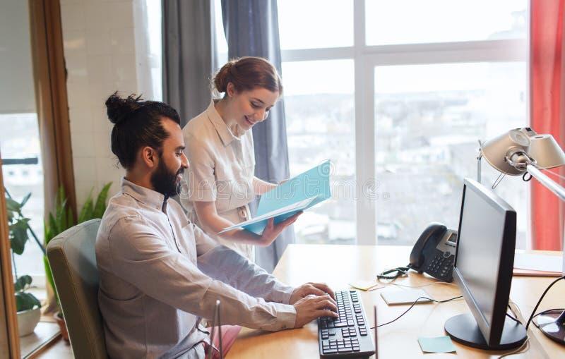 Glückliches kreatives Team mit Computer im Büro stockbild