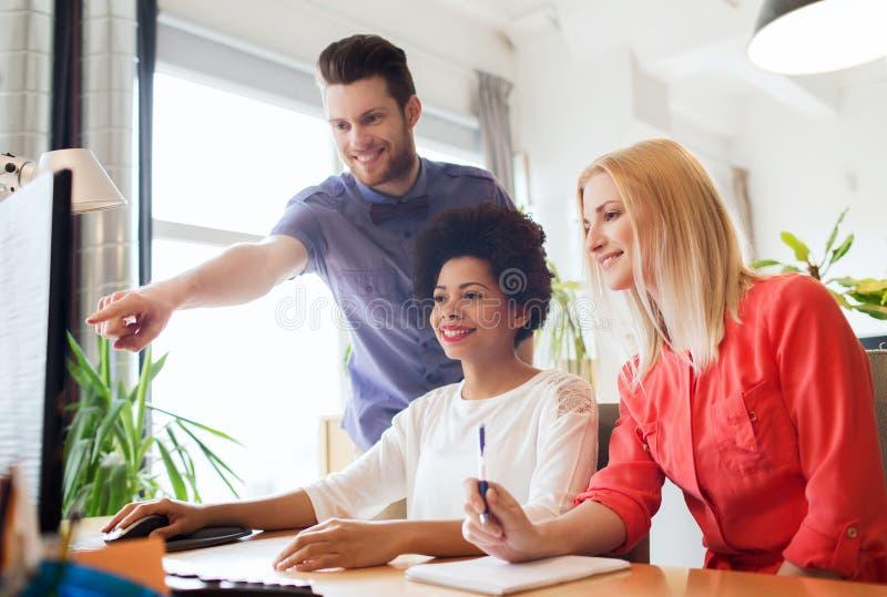 Glückliches kreatives Team mit Computer im Büro lizenzfreie stockfotos